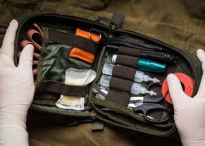 person wearing latex gloves opens first aid kit