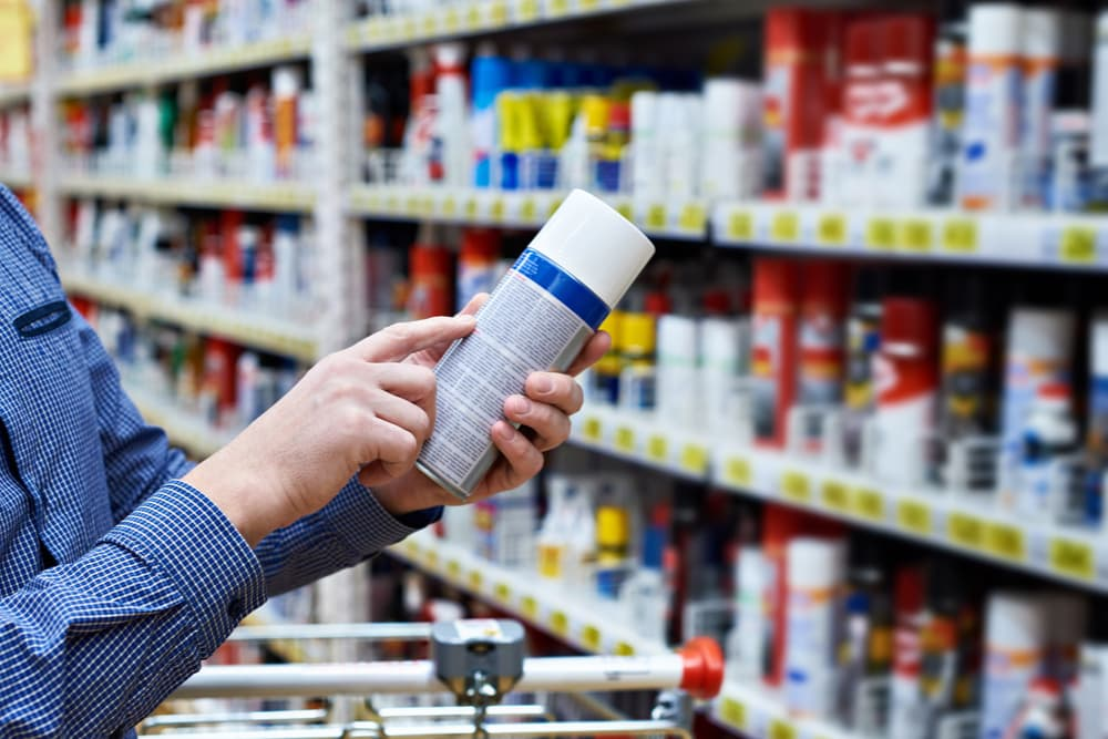 Man in aisle of shop checking a label