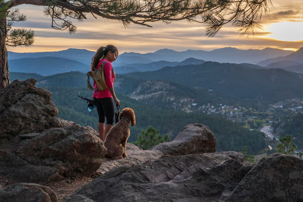 woman with dog hiking on cliff