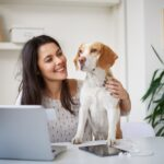 Woman researching on computer with dog