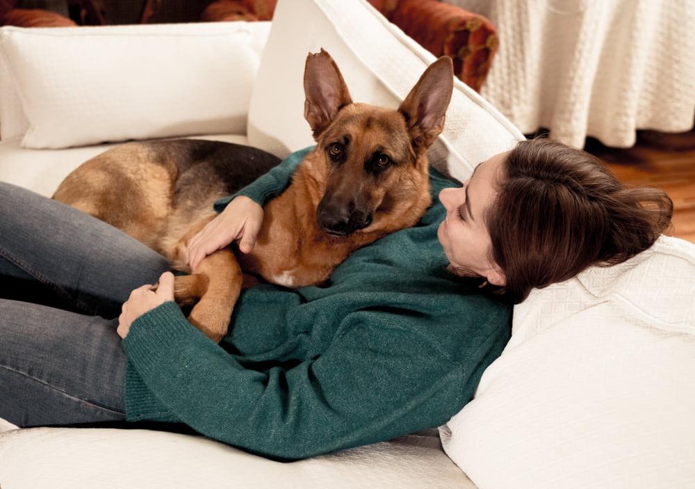 Woman cuddling with German Shepherd
