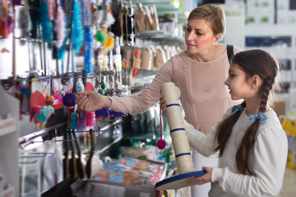 Young girl shopping with her mom for cat things in a pet store