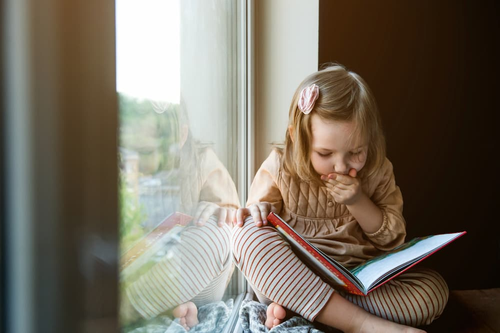 Little girl reading a book by a windowsill