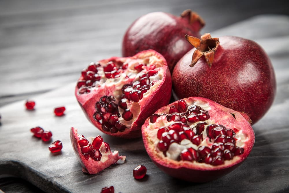 Open pomegranates on a table with seeds coming out the flesh